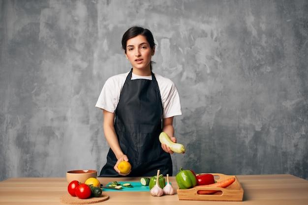 Donna in grembiule nero pranzo a casa insalata di cibo vegetariano