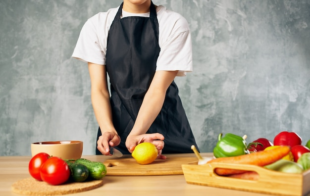 Donna in grembiule nero per affettare verdure cucina cucina cibo fresco.