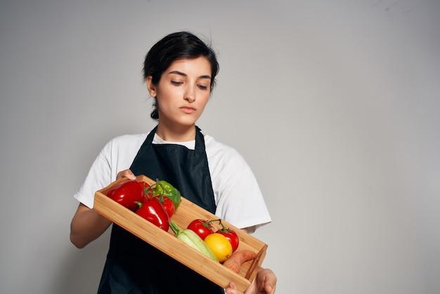 Donna in grembiuli neri verdure cibo sano stile di vita. foto di alta qualità