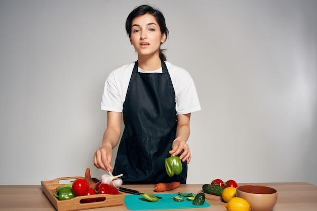 Donna in grembiuli neri verdure cucina cibo sano