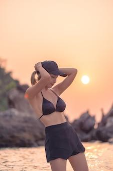 Donna in bikini nero in posa sulla spiaggia rocciosa nell'oceano sullo sfondo arancione del tramonto.