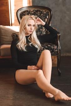 Donna in un body nero. sensuale splendida giovane signora in posa in studio