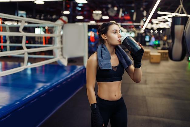 La donna in bende di boxe nere beve l'acqua sul ring, box training. pugile femminile in palestra, kickboxer ragazza nel club sportivo, allenamento kickboxing