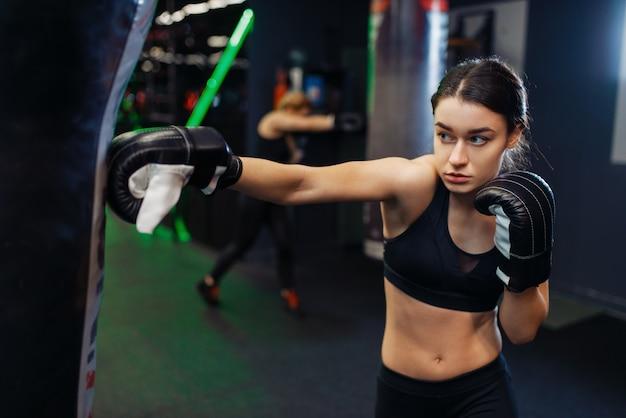 Donna in bende da boxe nere e abbigliamento sportivo colpisce un sacco da boxe, allenamento in box. pugile femminile in palestra, kickboxer ragazza nello sport club, pratica di pugni