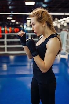 Donna in bende da boxe nere e abbigliamento sportivo sul ring, vista laterale, box training. pugile femminile in palestra, kickboxer ragazza nello sport club, pratica di pugni