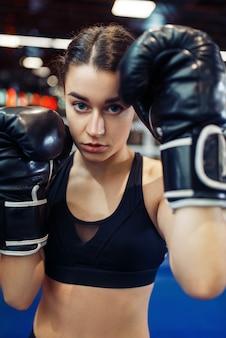 Donna in guantoni da boxe neri sul ring, vista frontale del primo piano, box training.