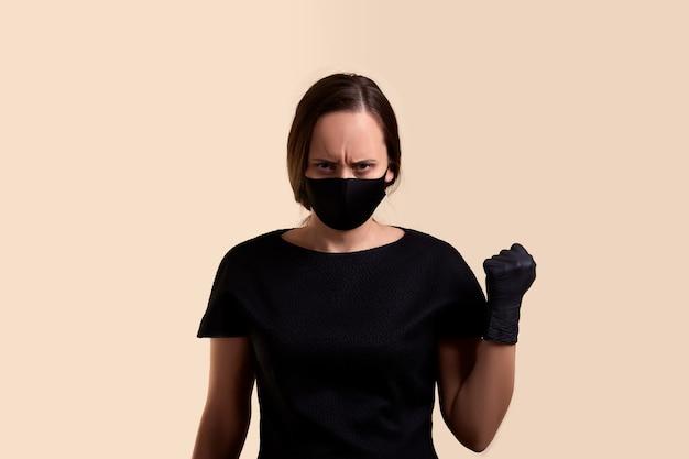 Donna in abito nero e maschera facciale nera minaccia con un pugno e oltre il muro beige
