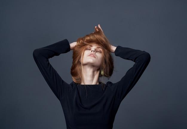 Donna abito nero fascino acconciatura alla moda muro scuro sera.