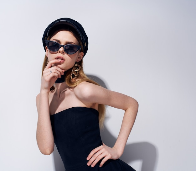 Donna in abito nero occhiali scuri parete leggera di lusso.