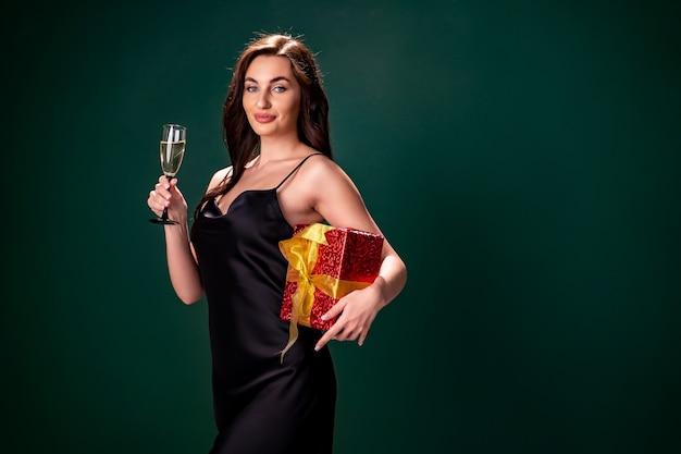 La donna in vestito nero tiene la scatola rossa del regalo e il bicchiere di champagne party time holiday concept