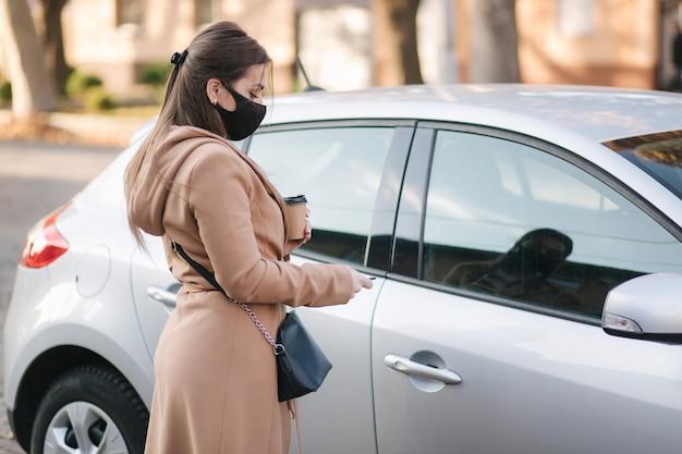La donna in maschera facciale nera tiene il caffè in macchina e guarda la chiave della macchina.