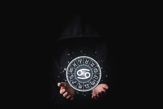 Una donna in un mantello nero con i suoi palmi tiene i segni astrologici luminosi degli zodiaci