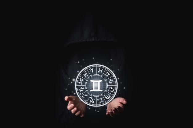 Una donna in un mantello nero con i palmi delle mani tiene i segni astrologici luminosi