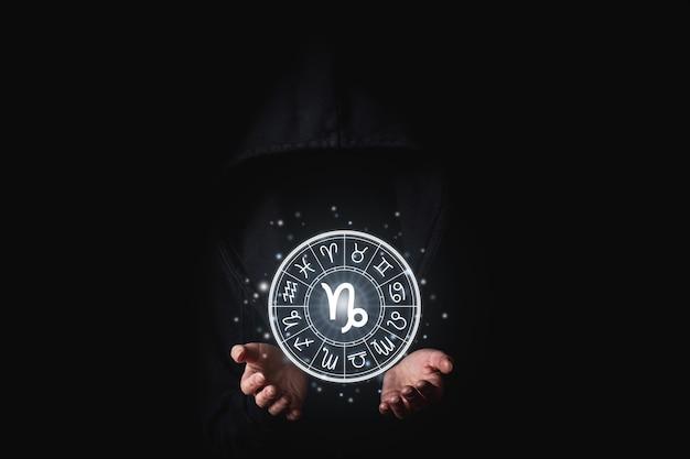 Una donna in un mantello nero con i palmi delle mani tiene lo sfondo luminoso dei segni astrologici.