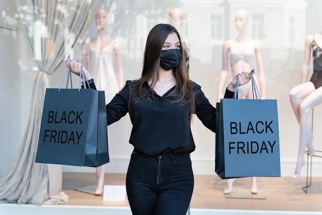 La donna in maschera nera e medica tiene le borse della spesa con l'iscrizione del black friday.