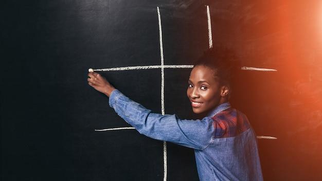 Donna nera gioca tic tac toe gioco divertimento intrattenimento afroamericano infanzia felice insegnante sviluppo del cervello precoce concept