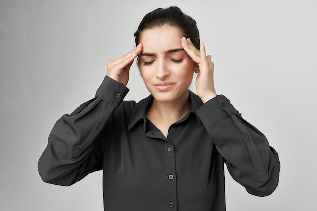 Donna in camicia nera mal di testa malcontento problemi sfondo isolato. foto di alta qualità