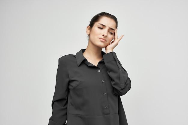 Donna in camicia nera che tiene la testa problemi di salute emozioni depressione