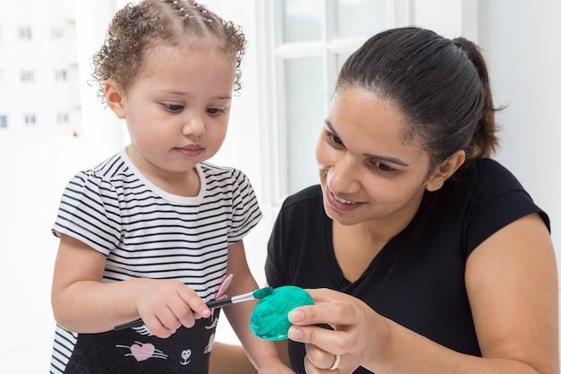 Donna in maglietta nera con il bambino che dipinge l'uovo di pasqua.