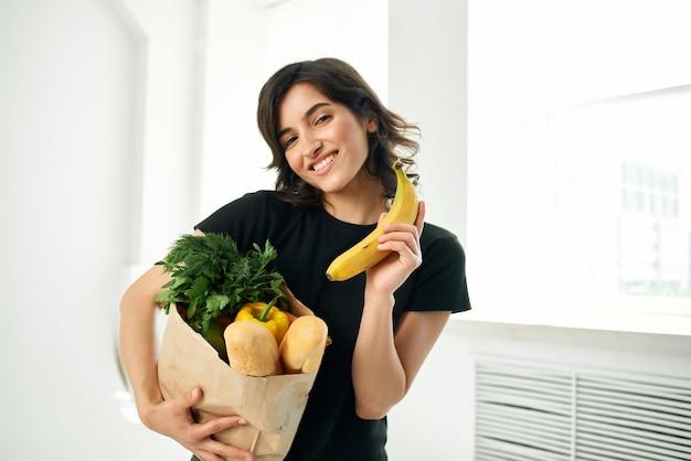Donna nel pacchetto della maglietta nera con i compiti della spesa per la spesa