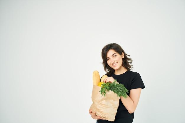 Donna in una maglietta nera con un pacco di generi alimentari nelle mani di una consegna