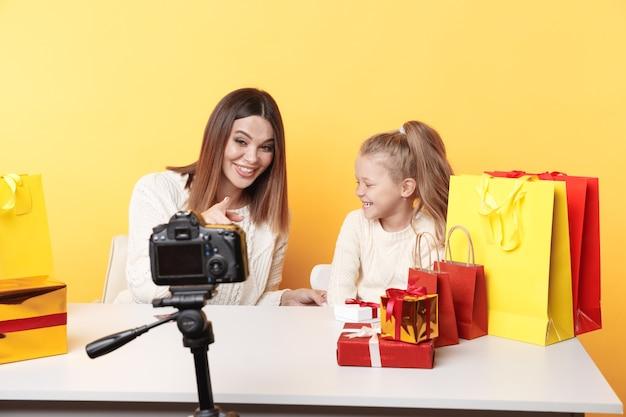 Blogger donna e bambina che registrano video sulla fotocamera insieme seduti in studio