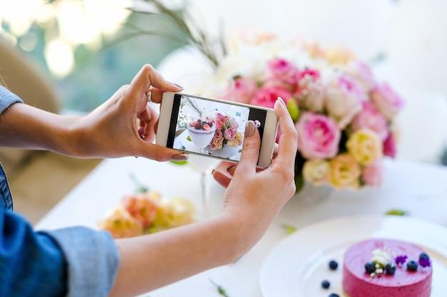 Concetto di pasticceria del partito della foto dello smartphone di blogger della donna. processo di creazione