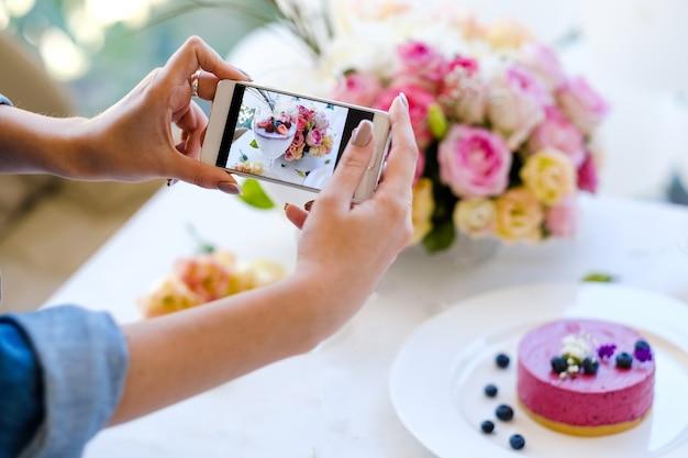 Concetto di pasticceria del partito della foto dello smartphone di blogger della donna. processo di creazione Foto Premium