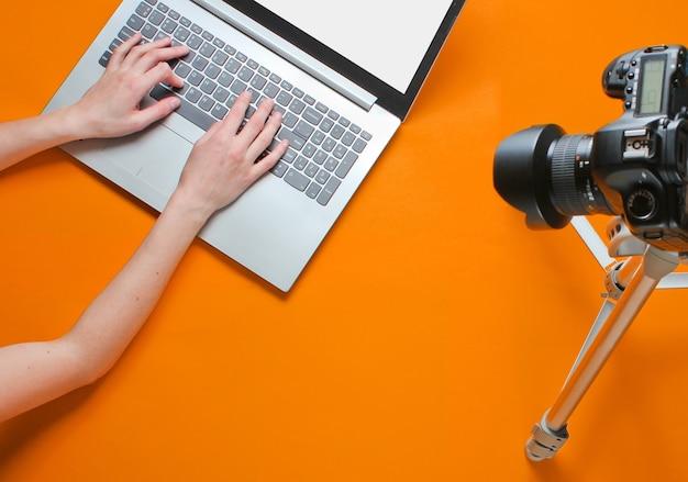 Blogger donna digitando su un laptop, blogging con una fotocamera con un treppiede su sfondo arancione. technoblogging. recensione del laptop. vista dall'alto