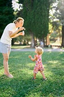La donna fa le bolle di sapone e la bambina le prende