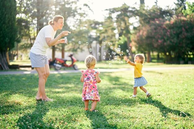 Una donna fa le bolle di sapone e due bambine le beccano in una radura