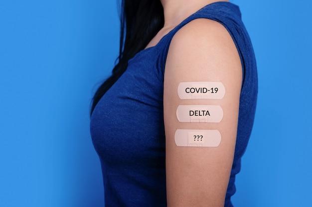 Donna su sfondo blu che mostra molti cerotti sulla spalla dopo il vaccino contro il coronavirus, nuovo concetto di francobolli, mutazione covid-19