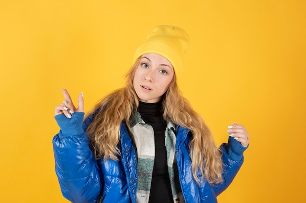 Donna in un cappotto blu e bennie giallo su sfondo giallo