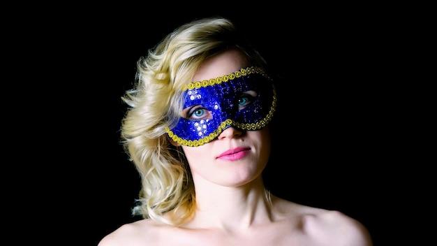 Donna in maschera per gli occhi azzurri con spalle nude