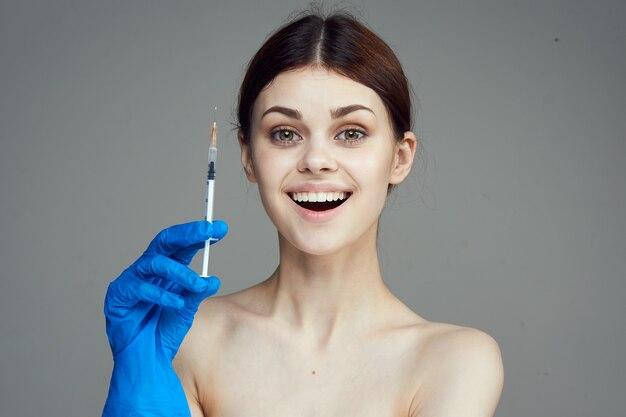 Donna in guanti blu con la siringa in mano con trattamento di iniezione di botox contro le rughe. foto di alta qualità
