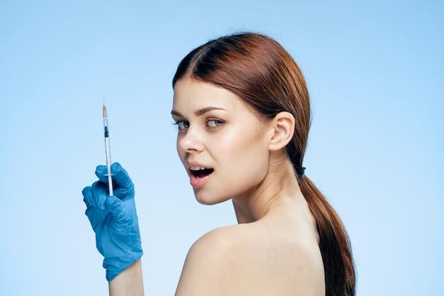 Donna in guanti blu con la siringa in mano con trattamento di iniezione di botox contro le rughe