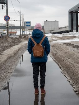 Una donna in giacca blu con uno zaino cammina per la città primaverile