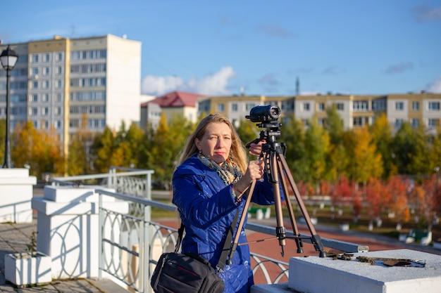 Donna in giacca blu con treppiede e videocamera riprende un paesaggio autunnale