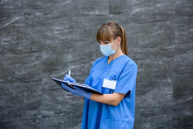 Donna in cappotto medico blu in posa su sfondo grigio in maschera con lo stetoscopio Foto Premium
