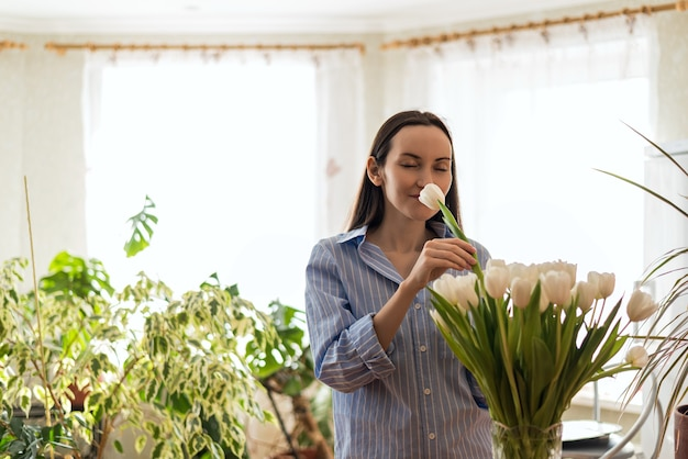 La donna in camicia blu inspira, annusa i tulipani bianchi, il concetto di fiori profumati, lo stile di vita dei fiori, godendo del concetto di aroma