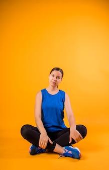 Una donna in divisa sportiva blu si siede e guarda davanti