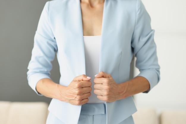 Donna in abito blu che tiene i bordi della giacca con il primo piano delle mani. stile aziendale per il concetto di donna