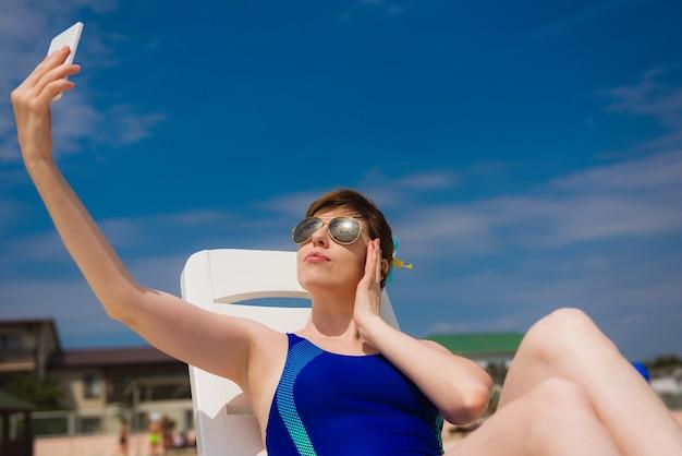 Donna in costume da bagno blu posa sulla terrazza solarium e prendendo selfie