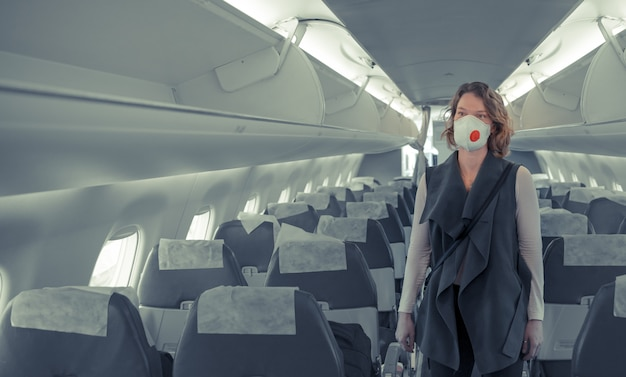 Donna a bordo di aeromobili con respiratore sulla testa. proteggersi dalle malattie virali. le persone annullano il viaggio all'estero a causa del coronavirus