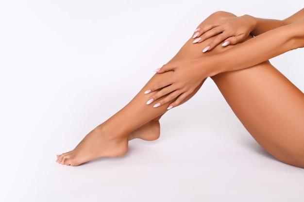 Cura del corpo della donna. chiuda in su delle gambe abbronzate femminili lunghe con pelle morbida liscia perfetta, pedicure, unghie sane su priorità bassa bianca. epilazione, ceretta, bellezza e concetto di salute