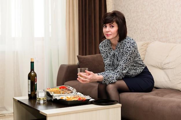 Donna annoiata a casa a tavola con un bicchiere di vino bianco, concetto di solitudine