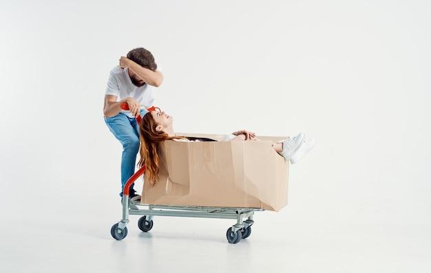 Donna in una scatola su un carrello da carico e corriere energico in jeans e t-shirt