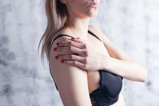 Una donna in reggiseno ha dolore alla spalla