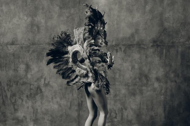 Donna in costume di carnevale samba brasiliana con piumaggio di piume. monocromatico con foto d'epoca a grana di pellicola,