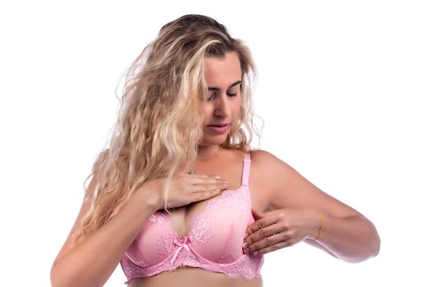 Auto cura ed esame del seno della donna per grumi o sintomi strani, con reggiseno rosa su uno bianco.